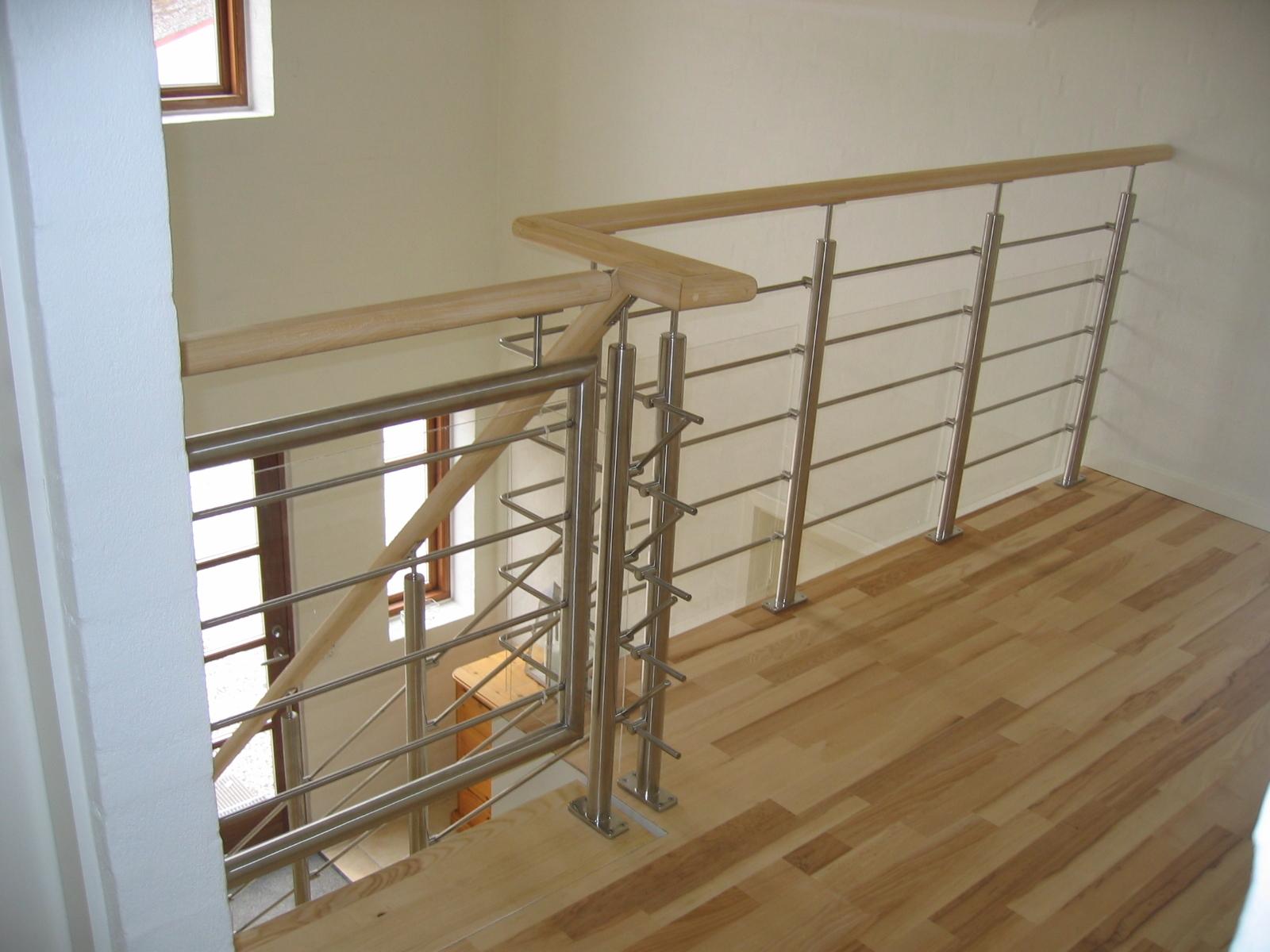 Rækværk til trappe udført i rustfast stål, træ og glas.