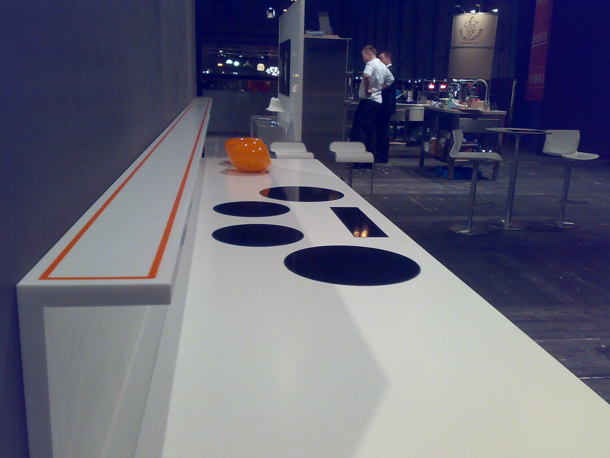 Dupont Corian bordplade med kogesektioner, påsvejst bagkant og krydderihylde. Kryderihylde er udført i to corianfarver.