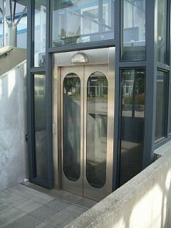 Elevatortårn udført af stål og glas. Inddækninger i rustfast stål og elevatordøre i glas og rustfast stål.