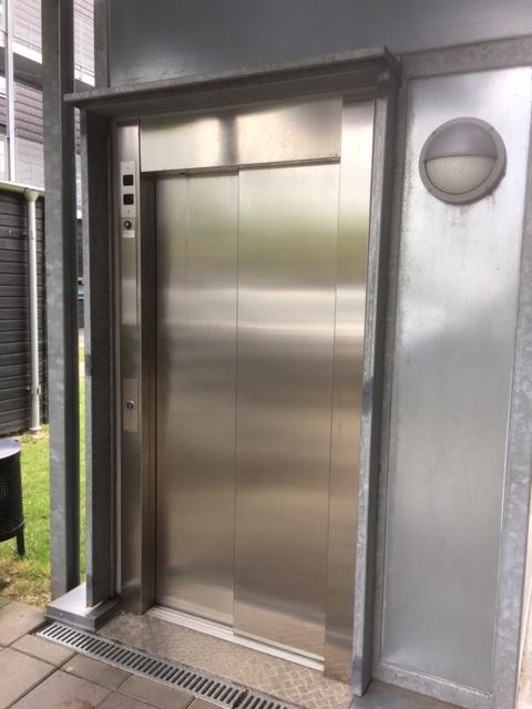 Indgang til elevator i rustfast stål.