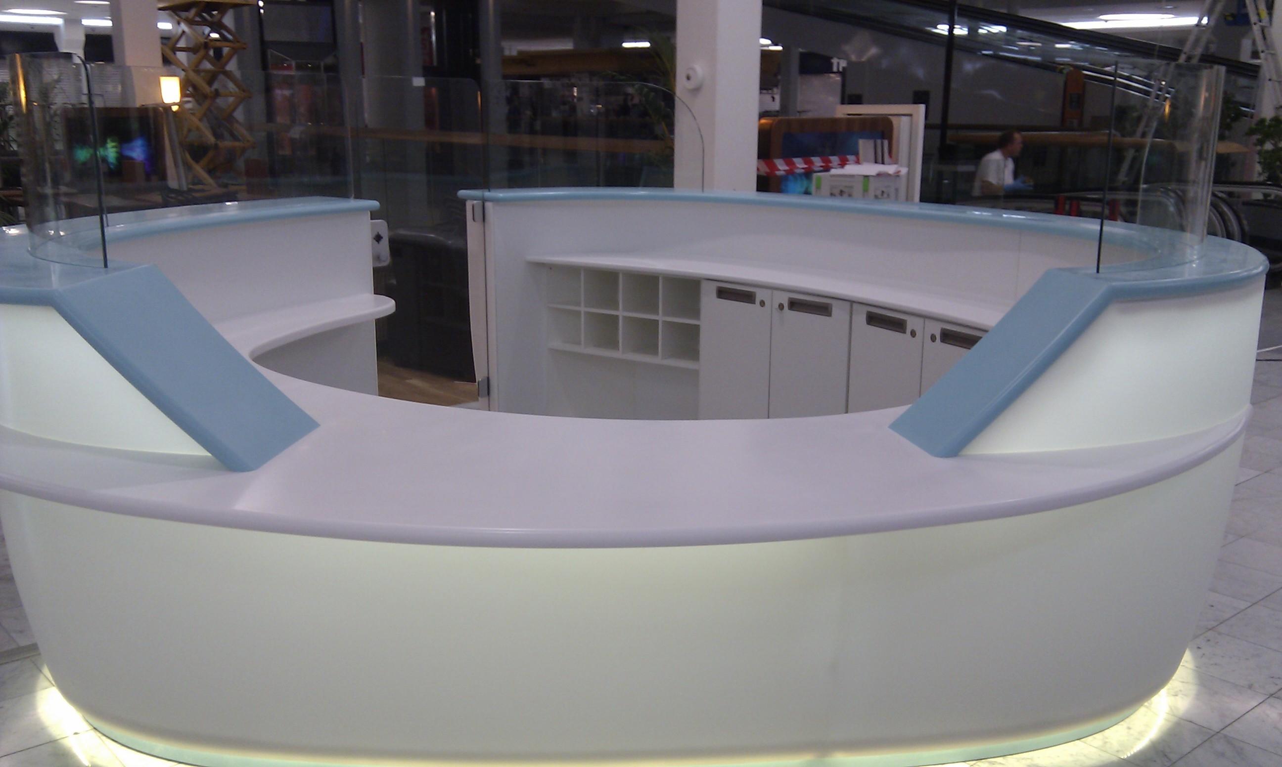 Receptionsdisk med lys udført i Dupont Corian og glas. Farver er Blueberry Ice, Strawberry Ice og Glacier Ice.